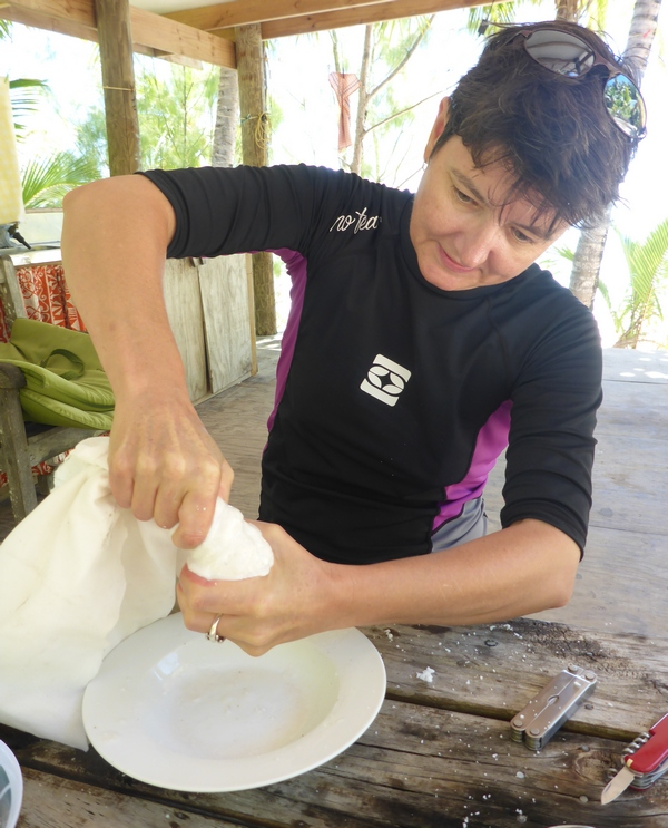 Squeezing freshly-grated coconut to make coconut cream